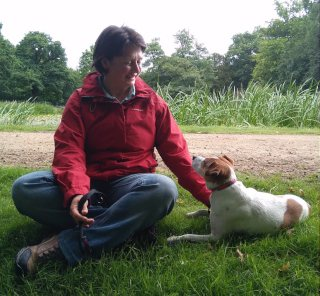 Zsuzsa with Daisy, her rescued Jack Russell cross, in a green meadow.